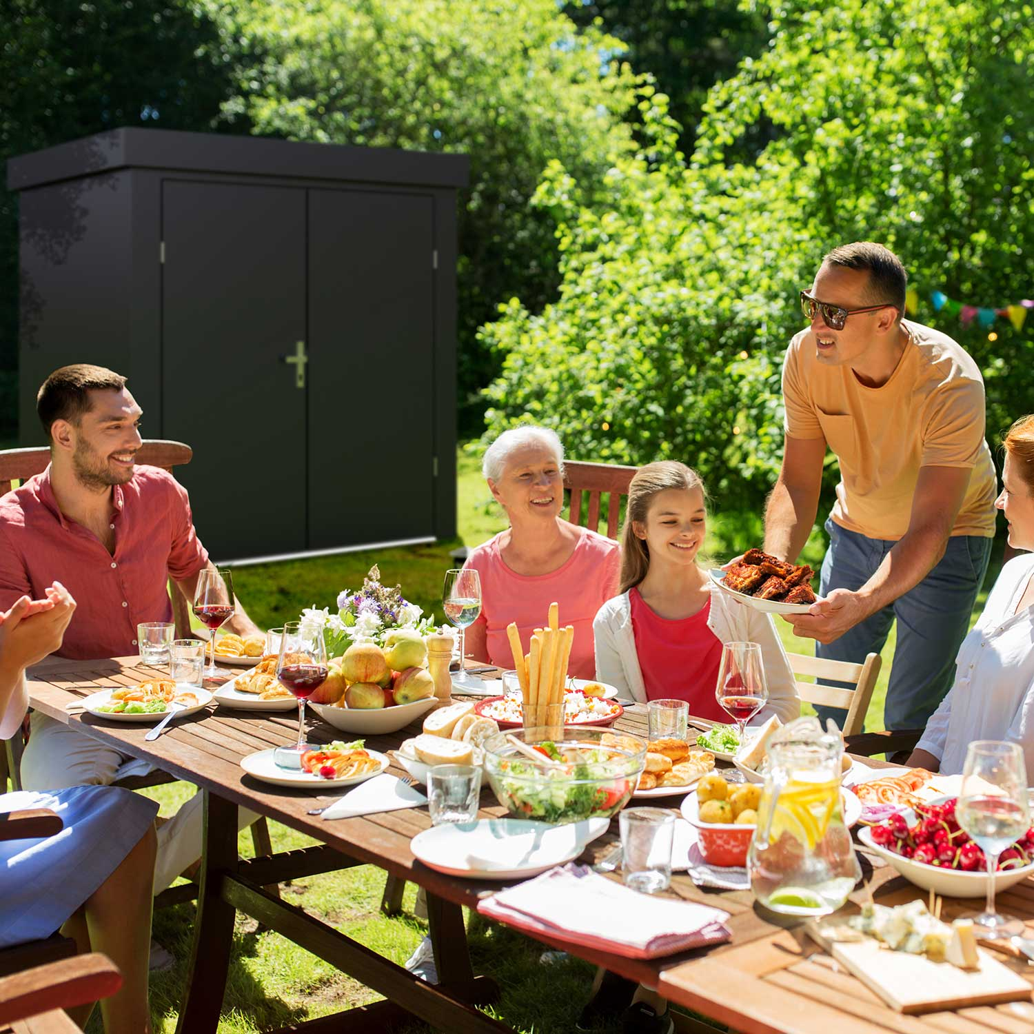 family having lunch in the garden / grey garden shed in the background